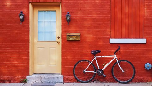 Bright yellow door in contrast to the red brick painted house, with a bicycle against the the wall