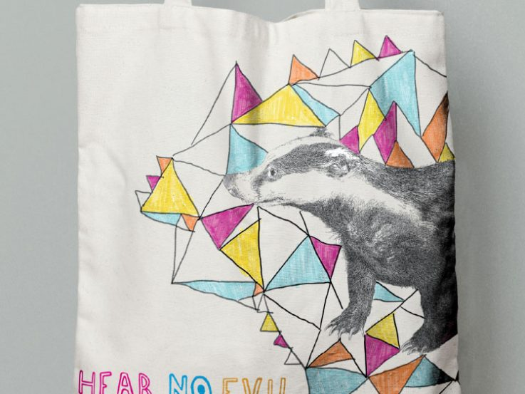 Branded canvas bag featuring badger illustration against a coloured shape background promoting the music festival.