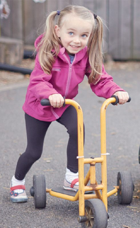 Fundraising supporter magazine smiling little girl on a scooter in the school playground.