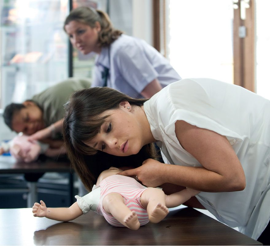 Teenage girl checking airways on a baby doll as part of her first aid training with St John Ambulance.