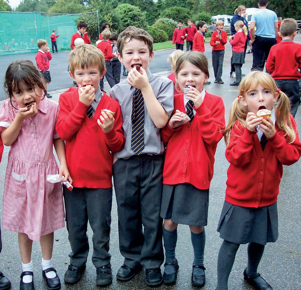 Primary school children eating cupcakes in their school uniform.