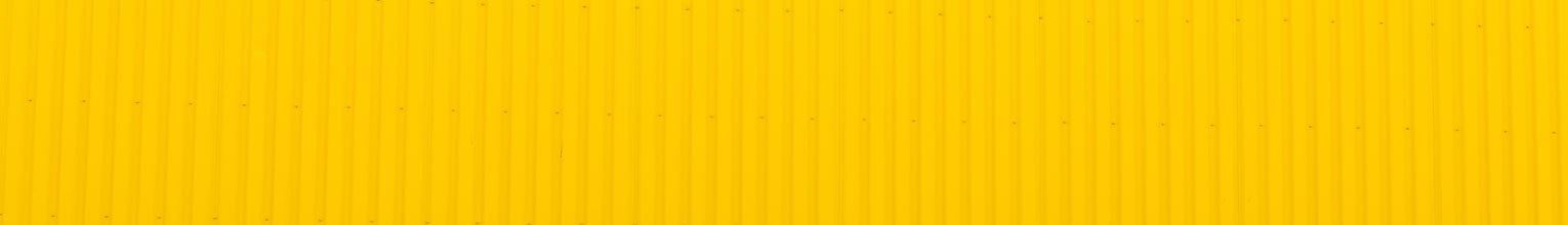 Repeating pattern on bright yellow corrugated fence.