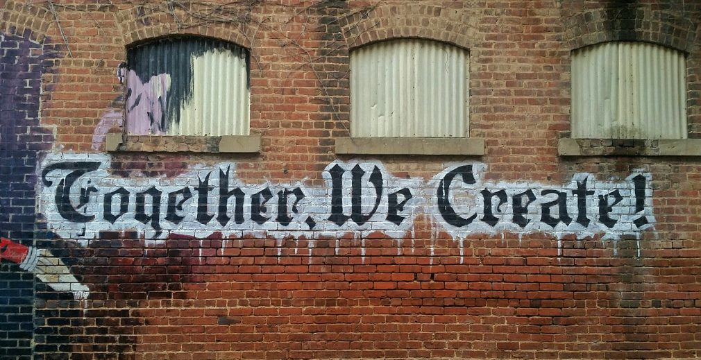 Graffiti on a wall saying Together we Create.