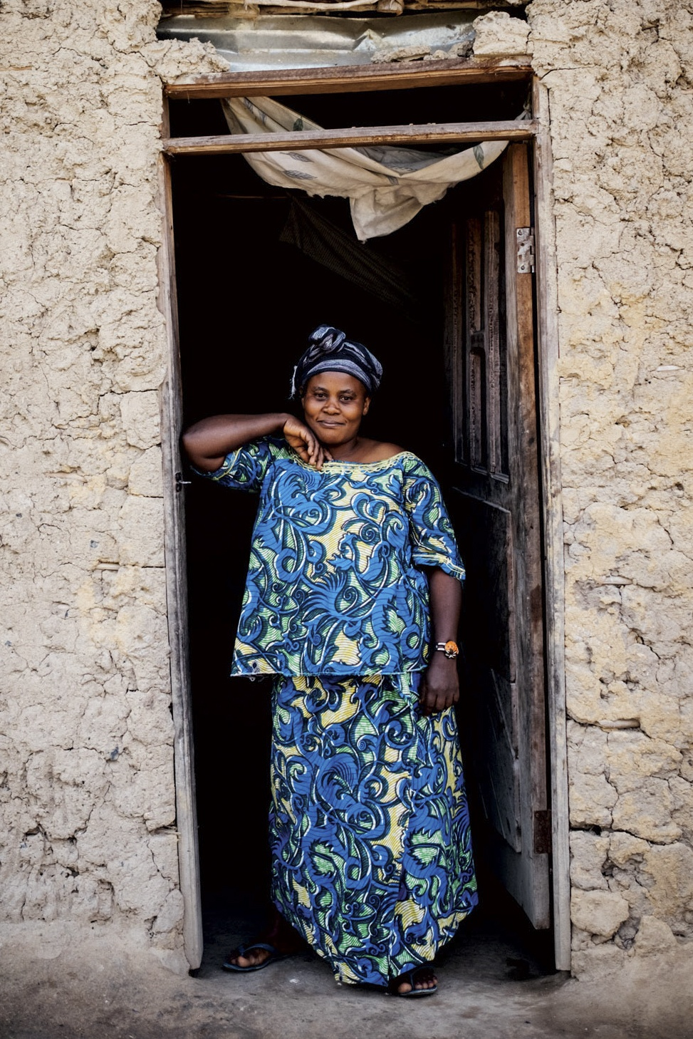 Woman standing in the doorway of a house.