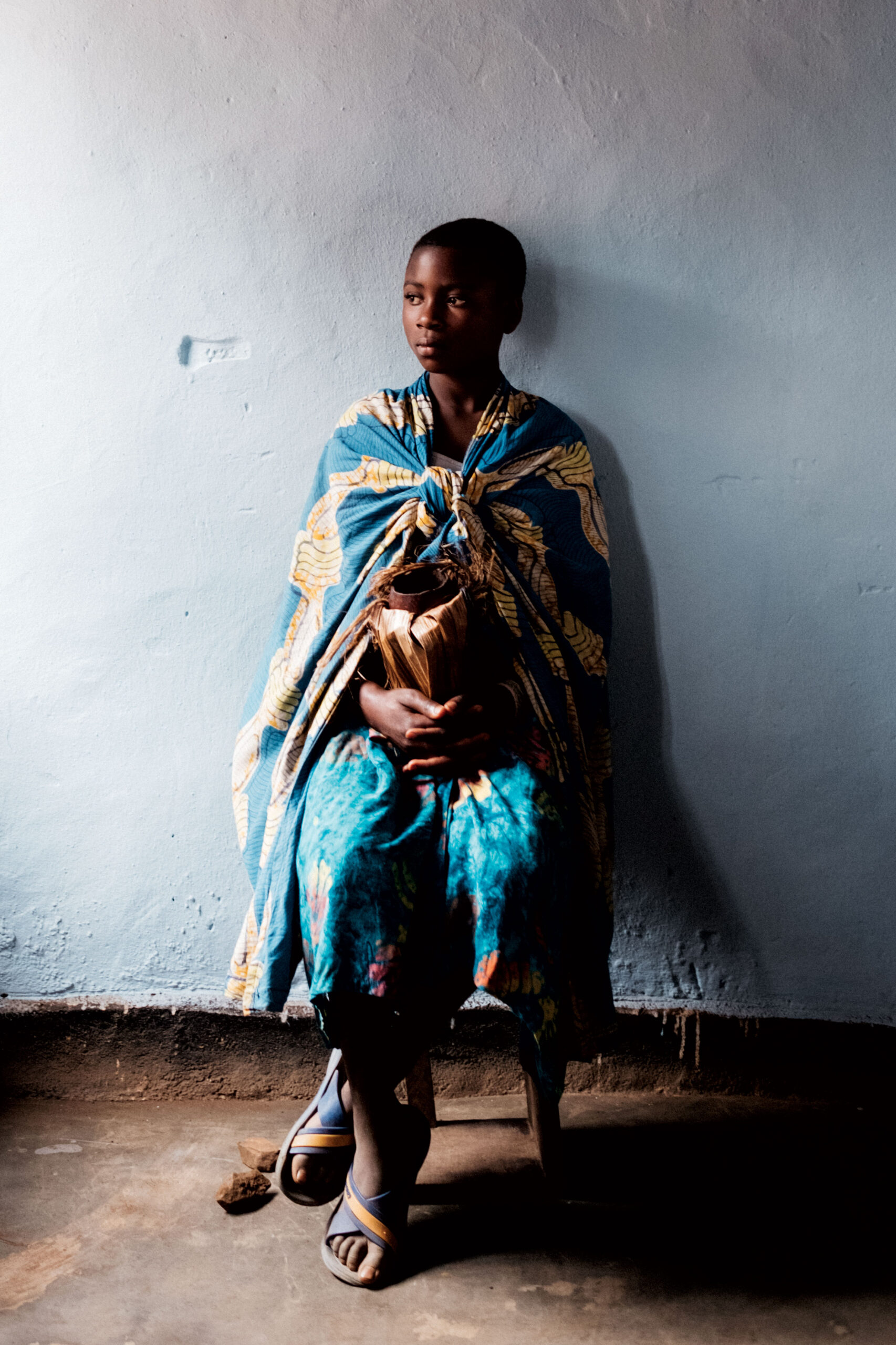 Young woman in traditional dress sitting on a chair.