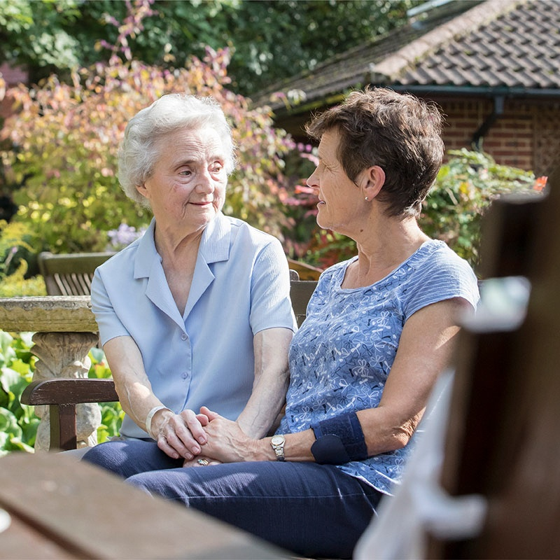 Two women in a Sue Ryder hospice looking at each other and holding hands