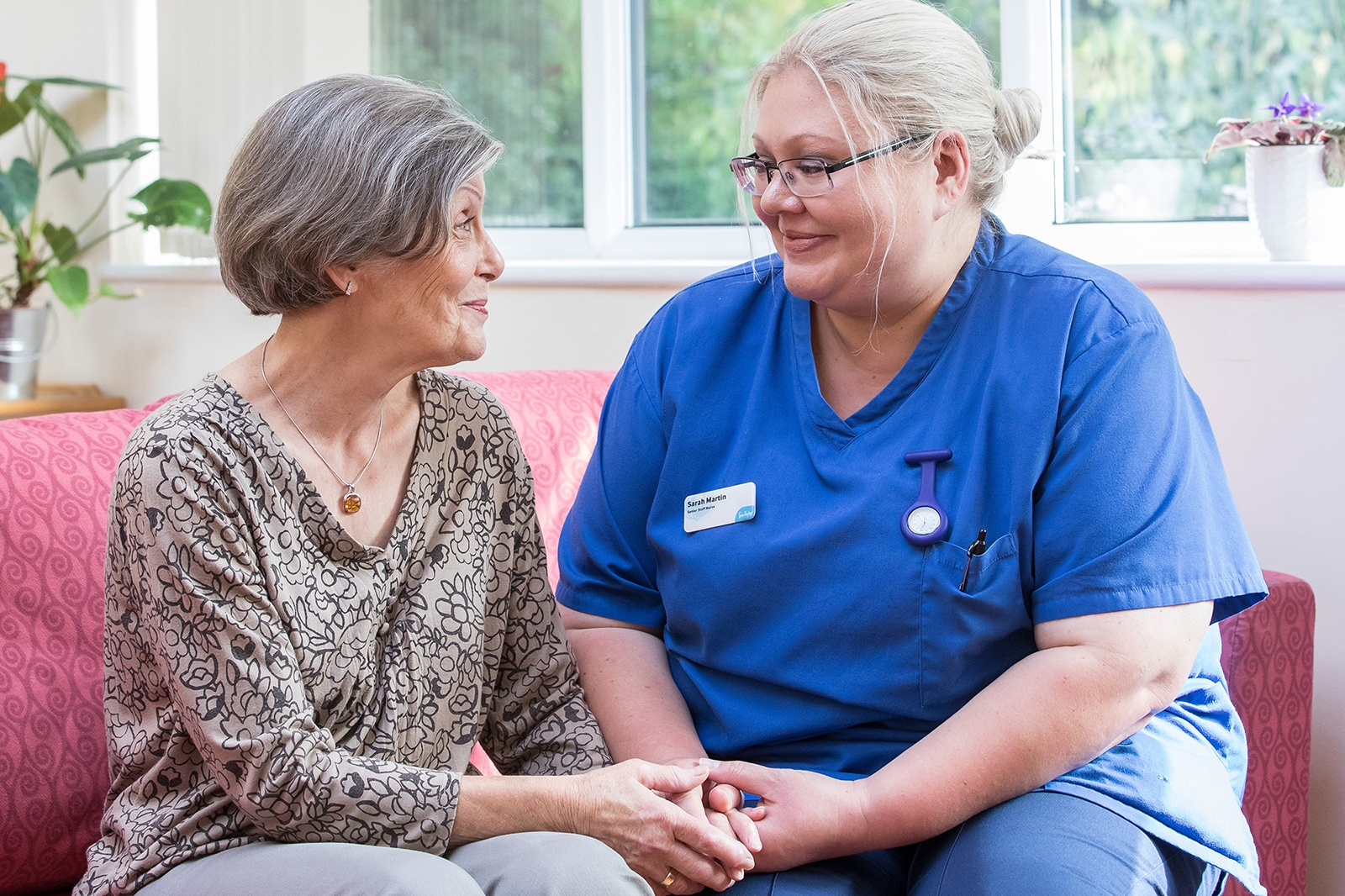 Image of a Sue Ryder nurse and patient smiling and holding hands