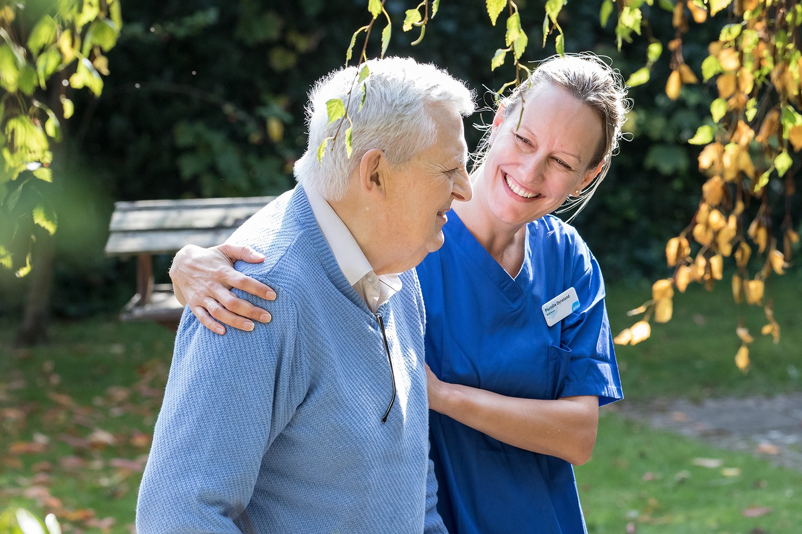 Image of a Sue Ryder nurse with her arm around a patient, both smiling in conversation