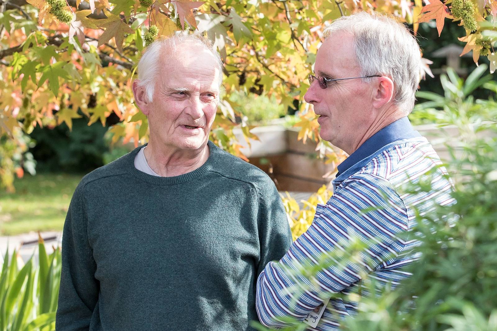 Image of two older men talking to each other